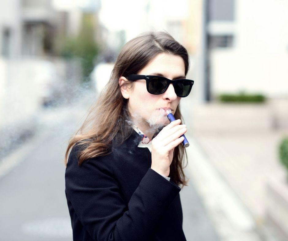 woman using a MTL vape pen for stealth vaping