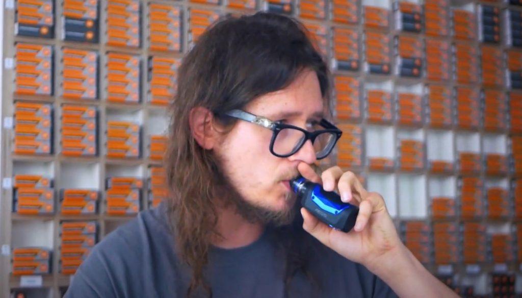 Man using a Geekvape Aegis for vaping