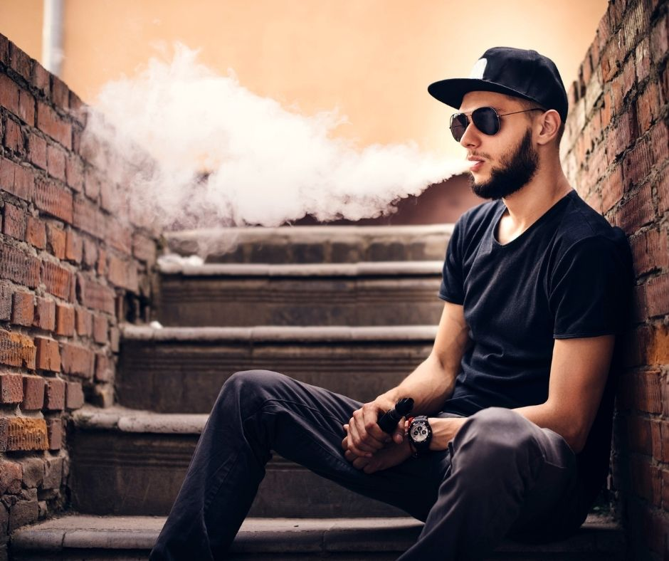 Man vaping on the stairs