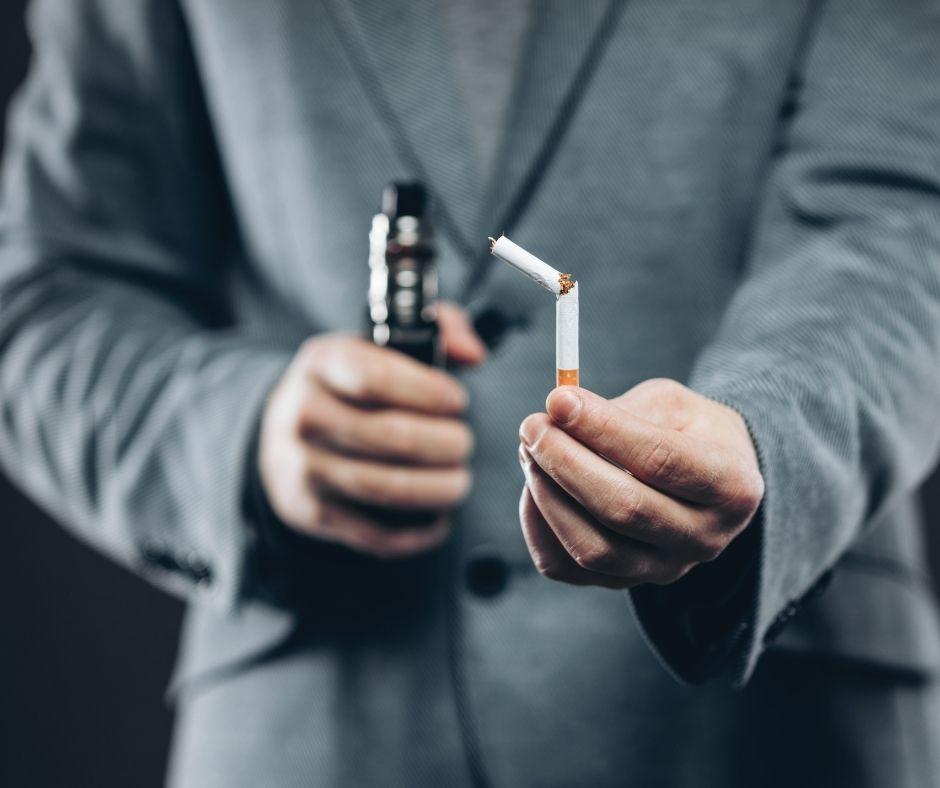 Man holding a vape and a broken cigarette
